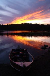 sunset over boat on gray lake on vancouver island camping